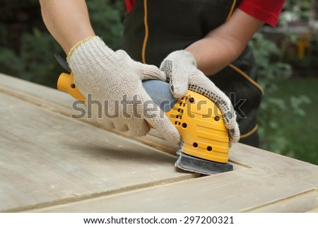 Closeup of worker hands sanding vintage wooden door with powertool - stock photo