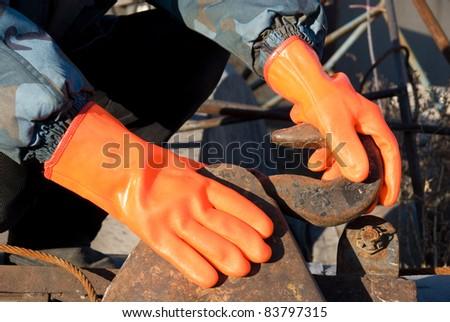 Closeup of worker man at orange gloves - stock photo