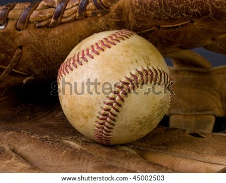 Closeup of worn baseball and old ragged glove - stock photo