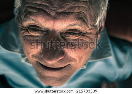 Closeup of wrinkled senior man face smiling. - stock photo