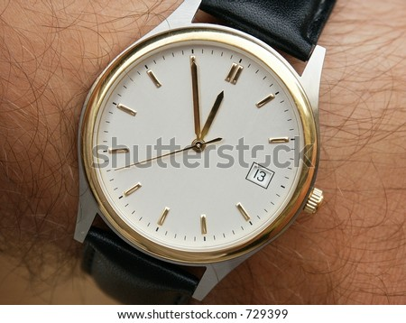 Closeup of Wrist Watch with white face. Hands on Five to Twelve... Calendar - 13.