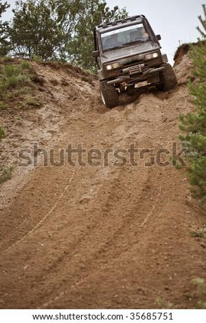 Closeup of 4x4 truck driving downhill trough mud - stock photo