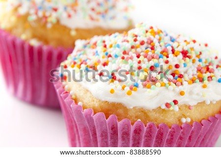 Closeup of yellow cupcake in pink wrapper with colorful sprinkles. - stock photo