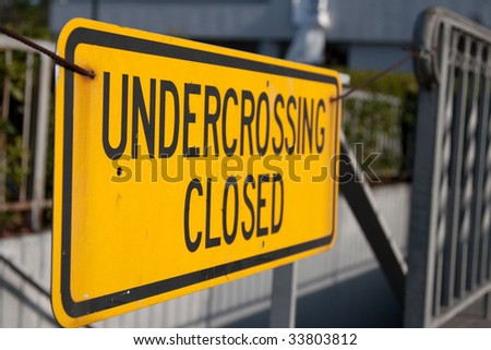 Closeup of yellow sign in front of subterranean pedestrian crossing - stock photo