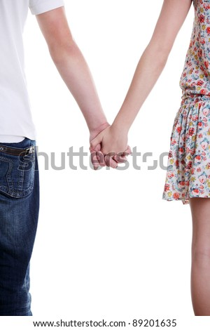 Closeup of young affectionate couple holding hands over white background. - stock photo