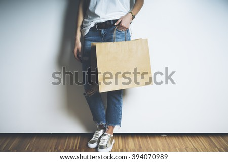 Closeup of young and stylish girl holding blank craft package, mock-up - stock photo