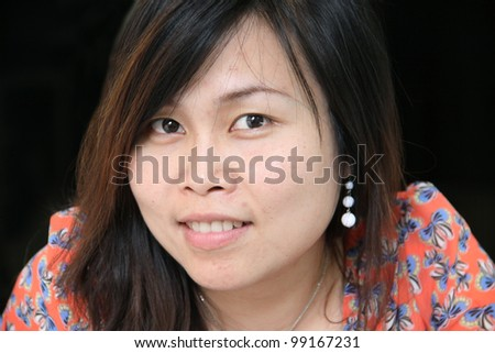 Closeup of young asian woman, isolated on black background - stock photo
