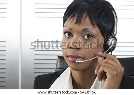 Closeup of young attractive african call center agent talking on the headset in a modern office setting - stock photo