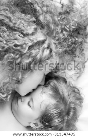 Closeup of young attractive loving mother with soft curly hair embracing small tiny cute male lovely baby sleeping indoor in bed with white linen black and white, vertical picture - stock photo
