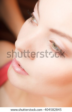 Closeup of young attractive woman face with lipstick on lips. Pretty gorgeous girl. Make up. - stock photo