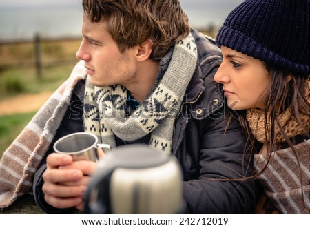 Closeup of young beautiful couple under blanket having hot beverage in a cold day with dark cloudy sky on the background - stock photo