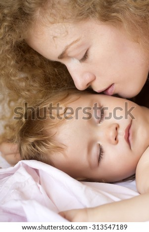 Closeup of young beautiful loving mother with light blonde curly hair kissing small tiny cute lovely baby boy sleeping indoor in bed with white linen lying close to each other, vertical picture - stock photo