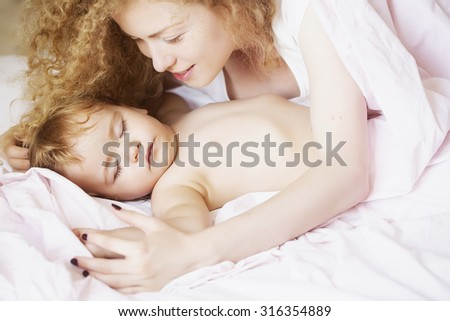 Closeup of young beautiful mother with light blonde curly hair sleeping with little tiny cute male lovely baby indoor in bed with white linen lying close to each other, horizontal picture - stock photo