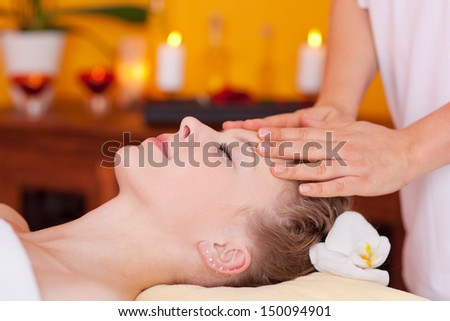Closeup of young beautiful woman receiving head massage treatment at a wellness center - stock photo
