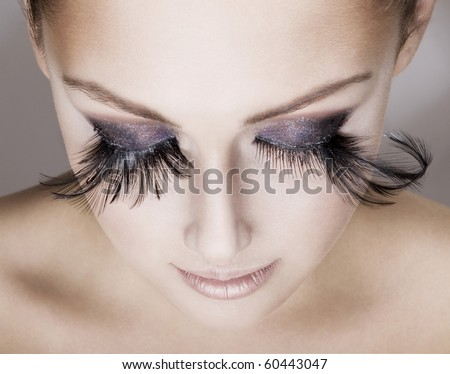Closeup of young beautiful woman  wearing false feather eyelashes. Woman's face looking down. - stock photo