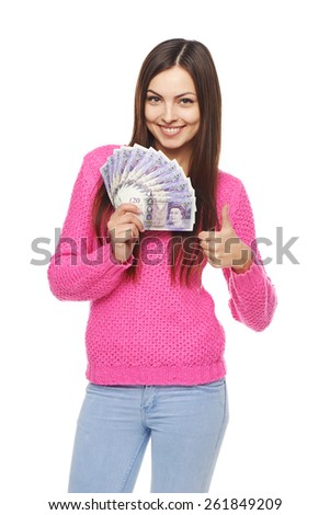 Closeup of young beautiful woman with British pounds in hand gesturing thumb up - stock photo