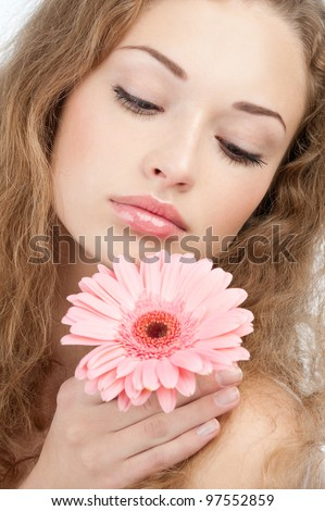 Closeup of young beautiful woman with healthy skin and long curly hair holding pink flower. Isolated on white background - stock photo