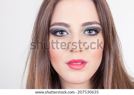 closeup of young blond girl wearing makeup looking at camera isolated on white