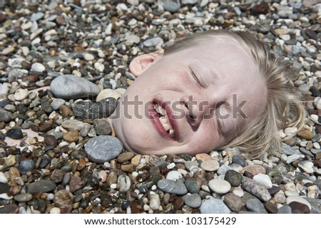 Closeup of young boy covered in pebbles on a beach - stock photo