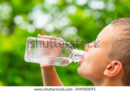 Closeup of young boy drinking pure tap water from transparent plastic drinking bottle while outdoors on a hot summer day. - stock photo