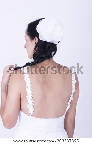 Closeup of young Bride with a sexy back and flower in the hair - stock photo
