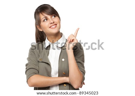 Closeup of young brunette businesswoman pointing at copy space, isolated on white background - stock photo
