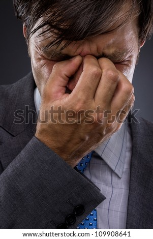 Closeup of young business man with headache rubbing temples