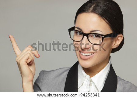Closeup of young business woman in eyeglasses pointing at copy space, over grey background - stock photo