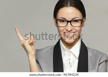 Closeup of young business woman in eyeglasses pointing at copy space, over grey background