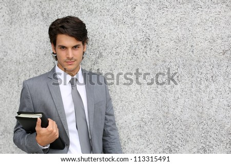 Closeup of young businessman leaning on wall - stock photo