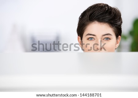 Closeup of young businesswoman looking at camera in cubicle at office - stock photo