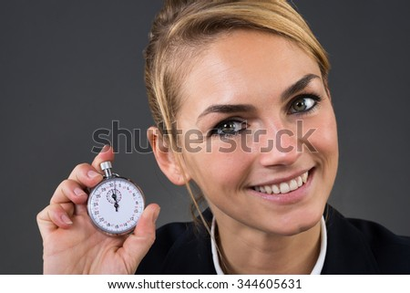Closeup of young businesswoman showing stopwatch over gray background - stock photo