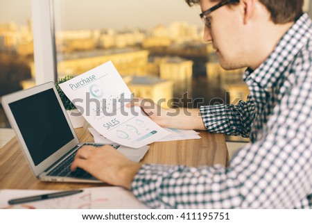 Closeup of young caucasian male copying information from business report to his computer with blank screen. Sunlit city background. Mock up - stock photo