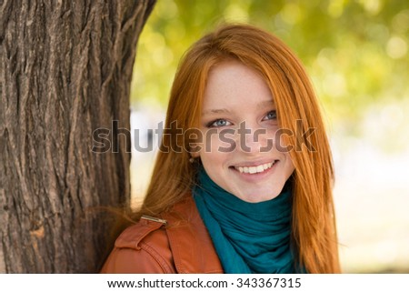 Closeup of young cheerful attractive woman standing near the tree in park - stock photo