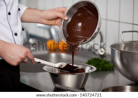 Closeup of young chef pouring liquid chocolate in bowl at commercial kitchen counter - stock photo