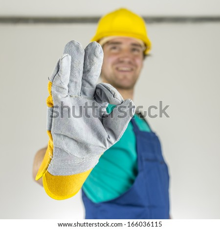 Closeup of young construction worker showing ok hand sign. - stock photo
