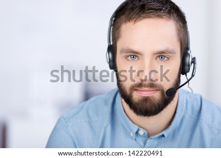 closeup of young customer service executive communicating on headset in office - stock photo