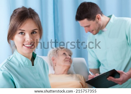 Closeup of young doctors and elder patient - stock photo