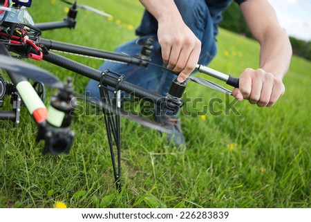 Closeup of young engineer tightening propeller of UAV drone with hand tool in park - stock photo