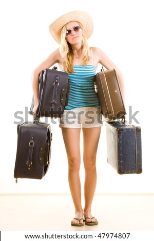 Closeup of young female holidaymaker in sunglasses and floppy hat carrying suitcases, isolated on white background.