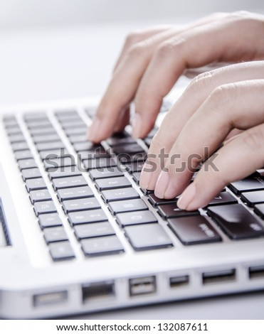 Closeup of young female typing on keyboard - stock photo