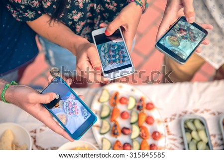 Closeup of young friends hands taking photos with their smartphones to vegetable skewers over a table in a outdoors summer barbecue - stock photo