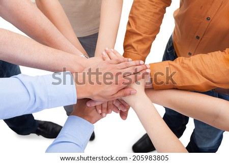 Closeup of young friends with their hands stacked together over white background - stock photo