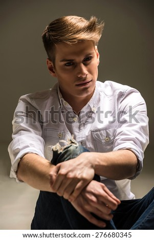 Closeup of young handsome man in shirt and jeans posing in the studio. Fashion portrait. - stock photo