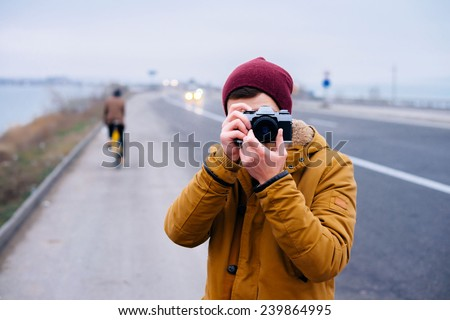 Closeup of young hipster man with digital camera outdoors. Young male photographer photographing nature - stock photo