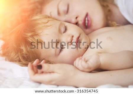 Closeup of young loving mother with light blonde curly hair holding small tiny cute lovely baby boy sleeping indoor in bed with white linen lying close to each other, horizontal picture - stock photo