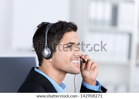 Closeup of young male customer service executive conversing on headset in office - stock photo