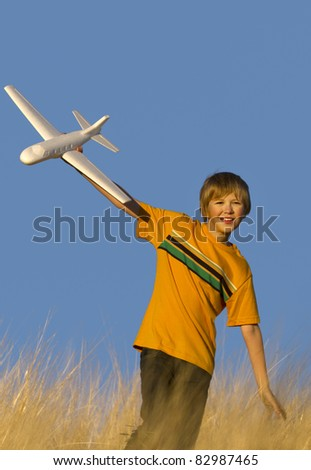 Closeup of young male in field playing with glider airplane. - stock photo