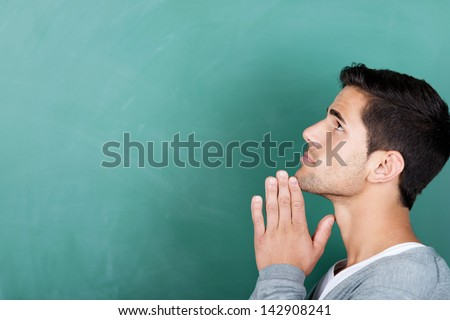 Closeup of young male student with hands clasped looking away against chalkboard in classroom - stock photo