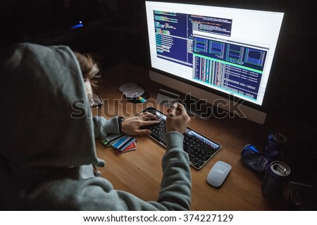 Closeup of young male theift in sweatshirt with hood transfering money from bills of stolen creding cards - stock photo